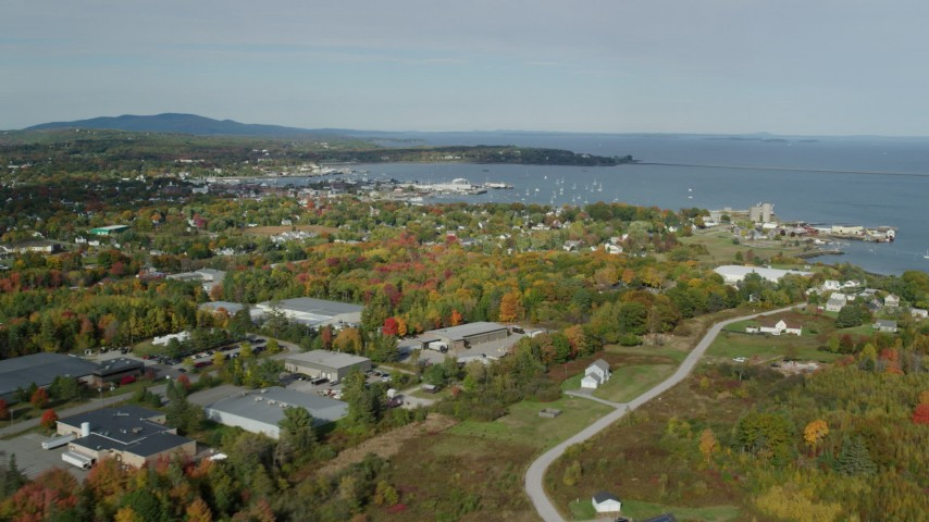6k stock footage aerial video flying by forest, warehouse buildings, small coastal town, autumn, Rockland, Maine Aerial Stock Footage | AX148_076