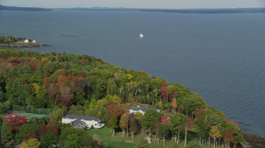 6k stock footage aerial video flying by foliage, a sailboat, West Penobscot Bay, autumn, Rockport, Maine Aerial Stock Footage | AX148_103