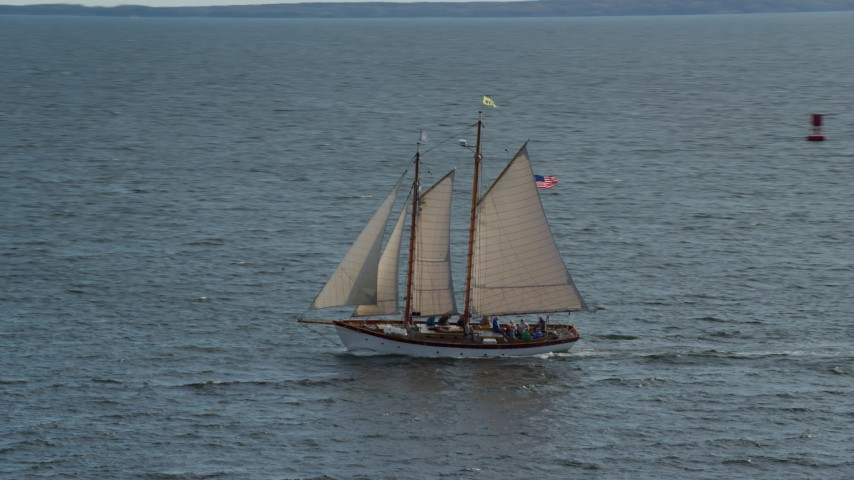 6k aerial video orbiting a sailboat on West Penobscot Bay, Rockport, Maine Aerial Stock Footage | AX148_106