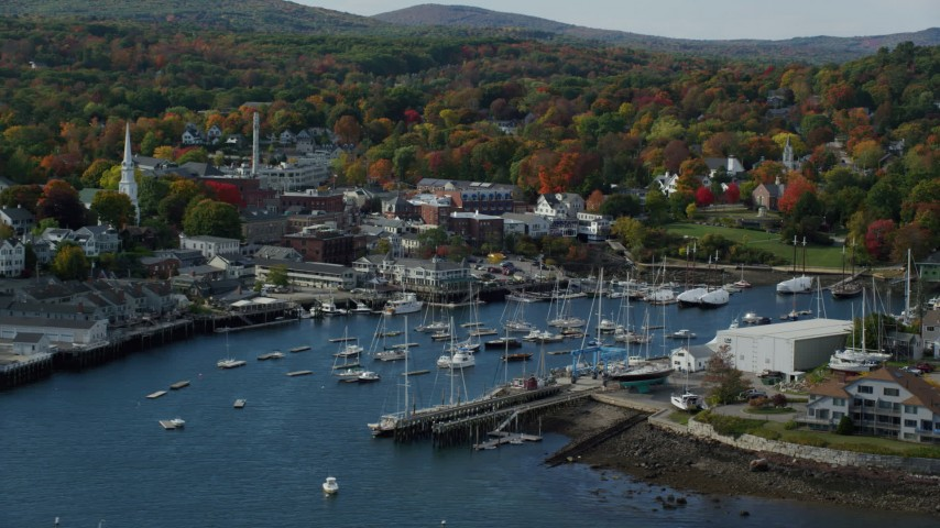 6k aerial video flying over Camden Harbor, approach small coastal town, autumn, Camden, Maine Aerial Stock Footage | AX148_111
