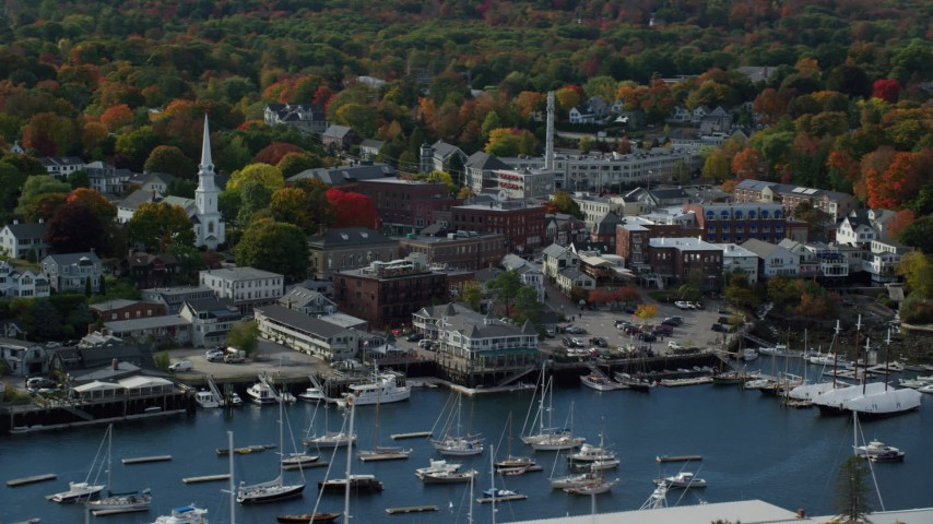6k aerial video flying by small coastal town near harbor, autumn, Camden, Maine Aerial Stock Footage | AX148_112