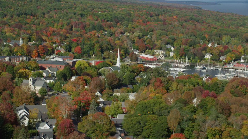 6k aerial video flying by small coastal town, Camden Harbor, autumn, Camden, Maine Aerial Stock Footage | AX148_119