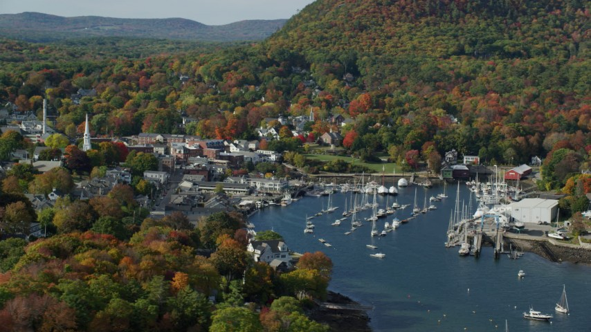 6k aerial video flying by small coastal town, boats in Camden Harbor, autumn, Camden, Maine Aerial Stock Footage | AX148_121