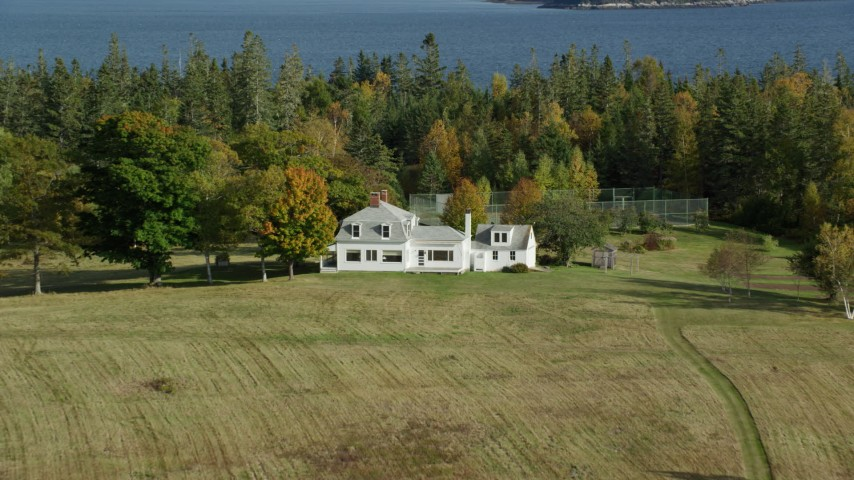 6k stock footage aerial video approaching an isolated home, tennis court, tilt down, autumn, Hog Island, Maine Aerial Stock Footage | AX148_135