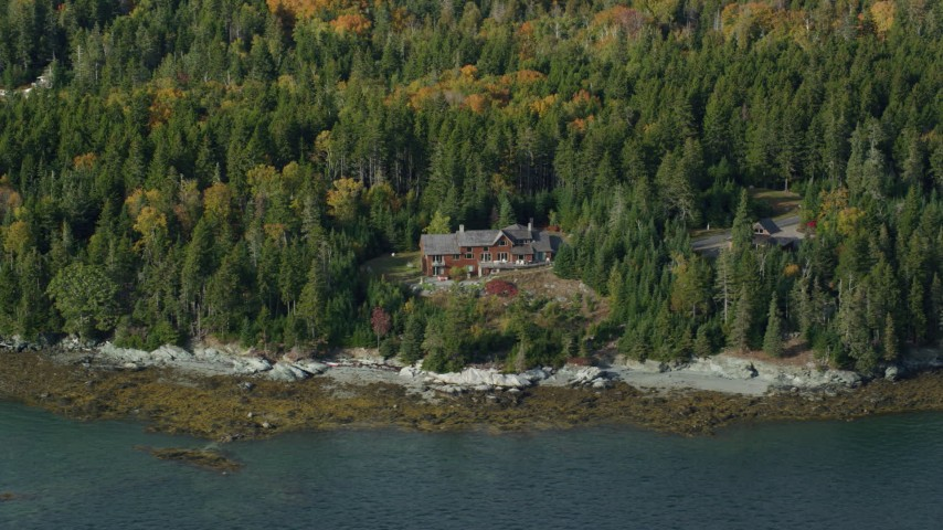 6k stock footage aerial video flying by a waterfront island home in autumn, Little Deer Isle, Maine Aerial Stock Footage   AX148_136