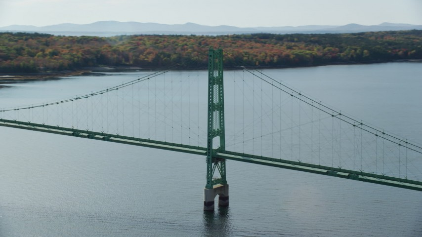 6k stock footage aerial video orbiting the Deer Isle Bridge, dense trees, autumn, Deer Isle Bridge, Maine Aerial Stock Footage | AX148_141