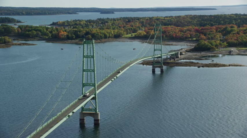 6k stock footage aerial video orbiting the Deer Isle Bridge, colorful trees in autumn, Little Deer Isle, Maine Aerial Stock Footage AX148_142
