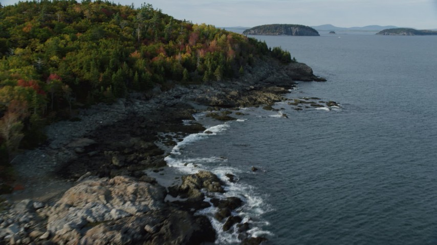 Flying by forested coastline, reveal waterfront mansion, Bar Harbor, Maine Aerial Stock Footage | AX148_188