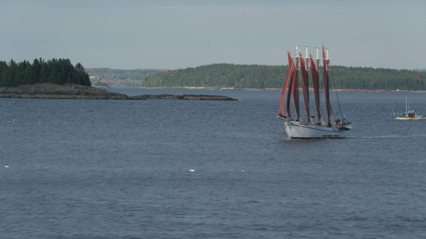 Tracking a sailing ship by a tiny island, Bar Harbor, Maine Aerial Stock Footage | AX148_195