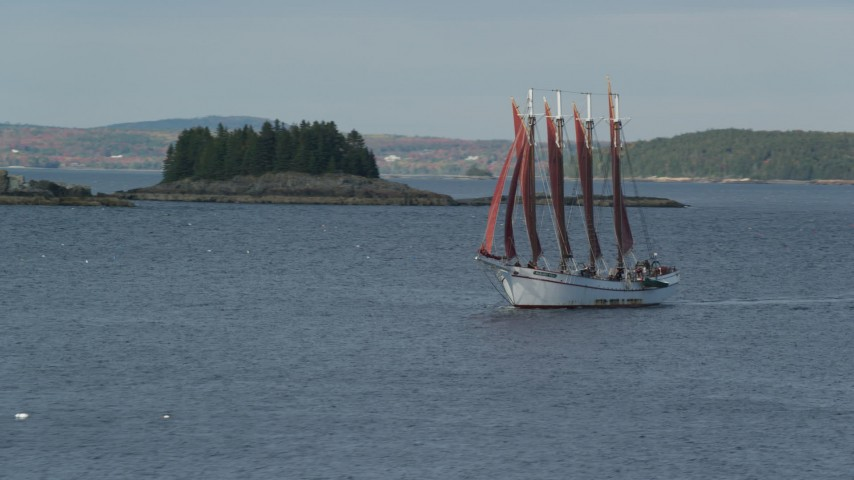6K aerial video tracking a sailing ship by a tiny island, Bar Harbor, Maine Aerial Stock Footage | AX148_195