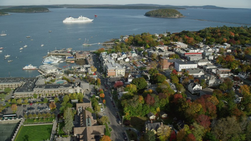 6K stock footage aerial video of a wide shot of a coastal town, harbor and cruise ship, autumn, Bar Harbor, Maine Aerial Stock Footage | AX148_203