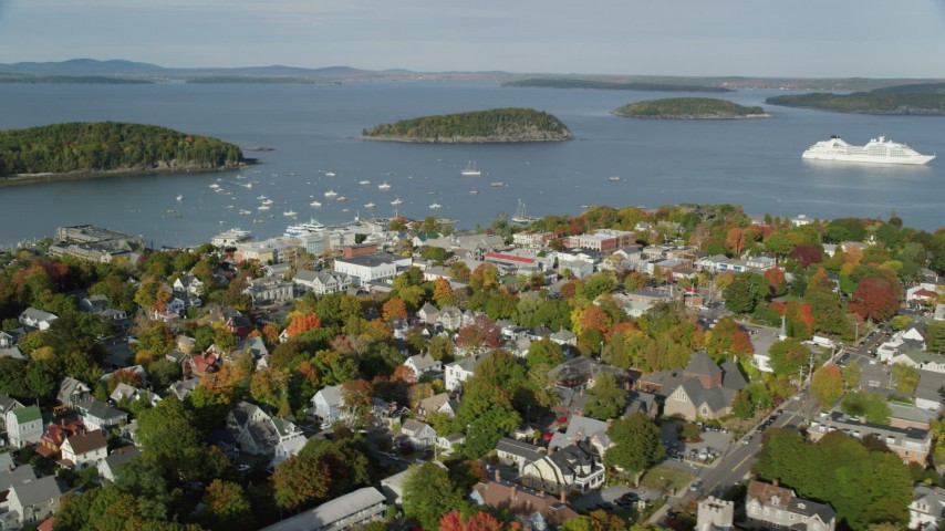 6K stock footage aerial video flying away from harbor and over coastal town with fall foliage, Bar Harbor, Maine Aerial Stock Footage | AX148_204