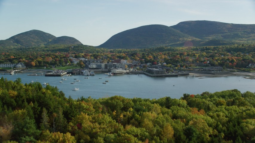 6K aerial video flying over color changing trees toward harbor and coastal town, autumn, Bar Harbor, Maine Aerial Stock Footage | AX148_211