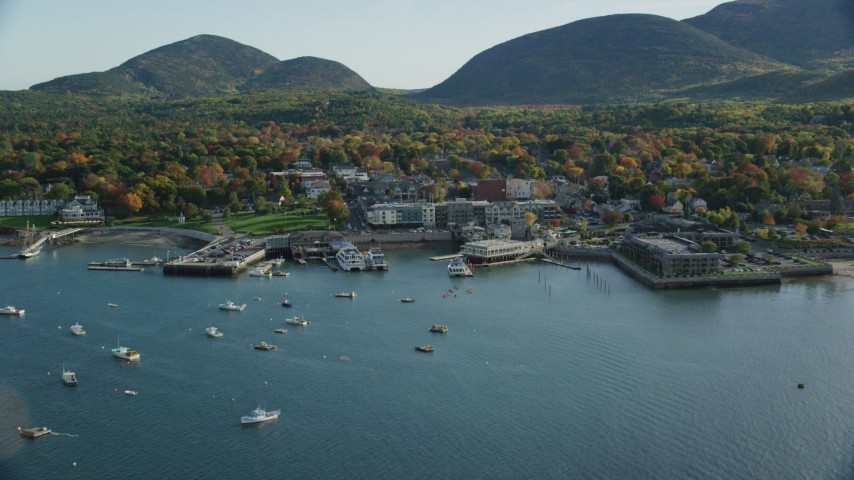 Fly over harbor toward small coastal town and fall foliage, autumn, Bar Harbor, Maine Aerial Stock Footage | AX148_212