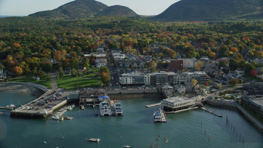 Fly over docked ferries toward Main Street in coastal town with fall foliage, Bar Harbor, Maine Aerial Stock Footage | AX148_213