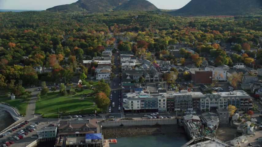 6K stock footage aerial video flying over docked ferries toward Main Street in coastal town with fall foliage, Bar Harbor, Maine Aerial Stock Footage | AX148_213