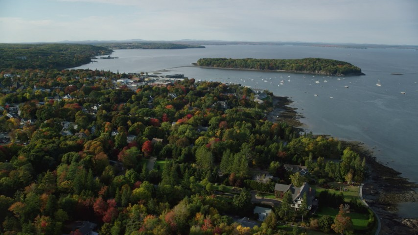 6K stock footage aerial video flying over fall foliage in a small coastal town toward harbor, autumn, Bar Harbor, Maine Aerial Stock Footage | AX148_217