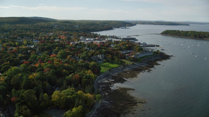 6K stock footage aerial video flying by coastal town with fall foliage and over the harbor, Bar Harbor, Maine Aerial Stock Footage AX148_218 | Axiom Images