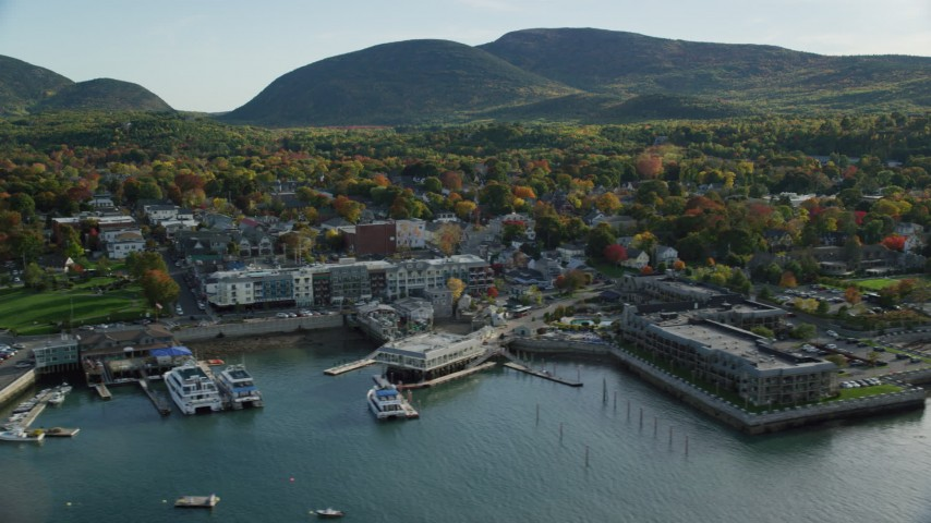Fly over harbor along coastal town, hotels, houses and fall foliage, Bar Harbor, Maine Aerial Stock Footage | AX148_221