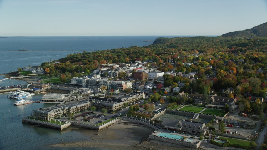 6K aerial video flying away from coastal town and hotel among fall foliage, revealing cruise ship, Bar Harbor, Maine Aerial Stock Footage AX148_222