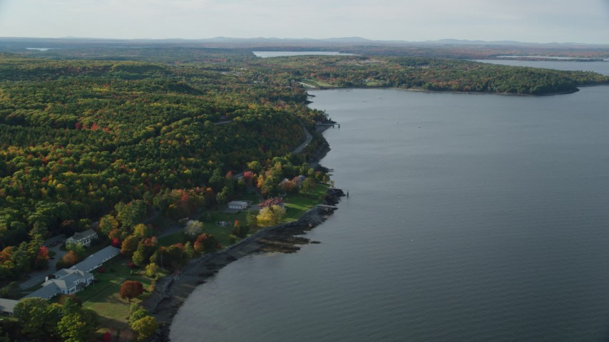 6K stock footage aerial video flying over water toward rode winding through forest with partial fall foliage, Bar Harbor, Maine Aerial Stock Footage | AX148_224