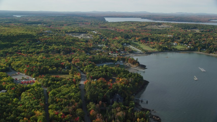 Fly over forest of partial fall foliage toward a coastal town, Bar Harbor, Maine Aerial Stock Footage | AX148_226