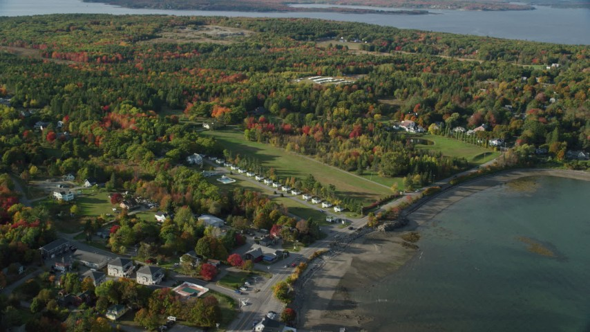 Approaching cottages among a coastal community and fall foliage, autumn, Bar Harbor, Maine Aerial Stock Footage | AX148_227