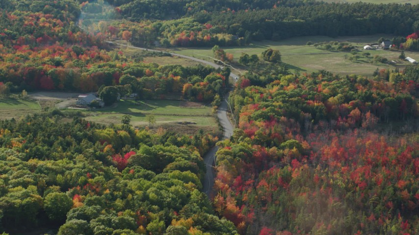 6K stock footage aerial video following a road through the countryside with fall foliage, Bar Harbor, Maine Aerial Stock Footage | AX148_228