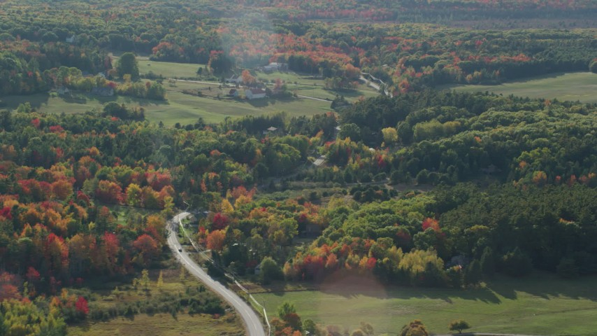 6K stock footage aerial video passing by a road winding through forest toward rural homes, fall foliage, Bar Harbor, Maine Aerial Stock Footage | AX148_229