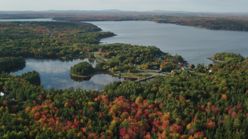 6K stock footage aerial video flying over fall foliage toward a pond and coastal town, Bar Harbor, Maine Aerial Stock Footage | AX148_230