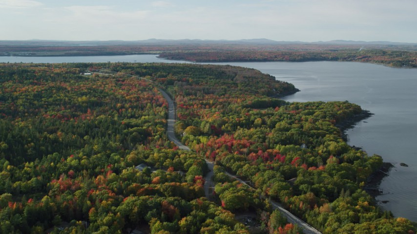 Fly over road winding through forest filled with fall foliage, Bar Harbor, Maine Aerial Stock Footage | AX148_231