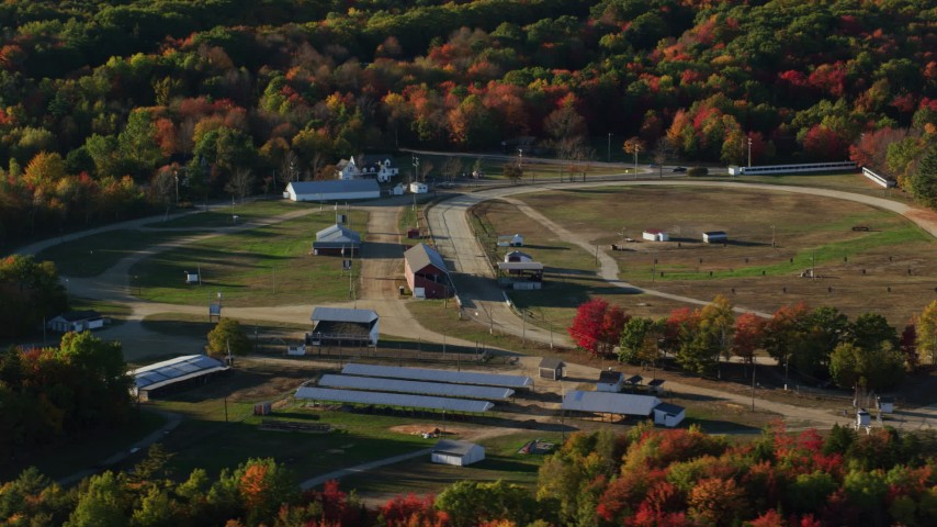 6K stock footage aerial video orbiting a race track and fairgrounds among fall foliage, Blue Hill, Maine Aerial Stock Footage AX149_016 | Axiom Images