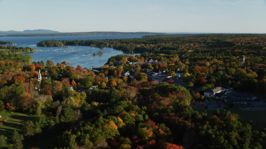 6K aerial video flying by coastal town and harbor among fall foliage, Blue Hill, Maine Aerial Stock Footage AX149_018