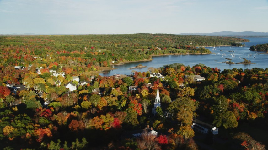 6K stock footage aerial video flying over fall foliage and a small coastal town near the harbor, Blue Hill, Maine Aerial Stock Footage | AX149_020