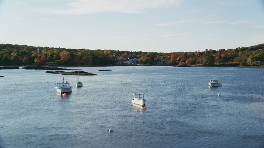 6K aerial video flying over boats in a harbor toward a coastal town, autumn, Blue Hill, Maine Aerial Stock Footage | AX149_025