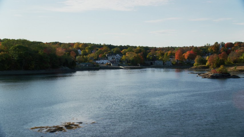 6K stock footage aerial video flying over water toward coastal town and fall foliage, Blue Hill, Maine Aerial Stock Footage | AX149_026