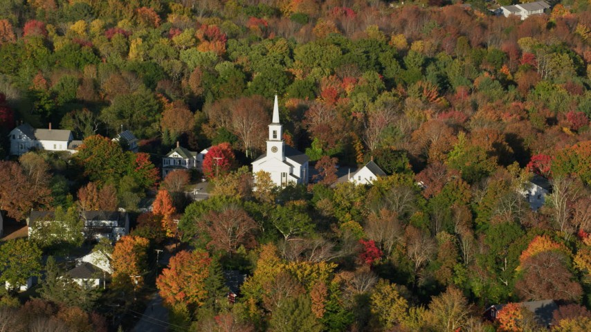 6K aerial video flying away from a small town and white church among fall foliage, Blue Hill, Maine Aerial Stock Footage | AX149_029