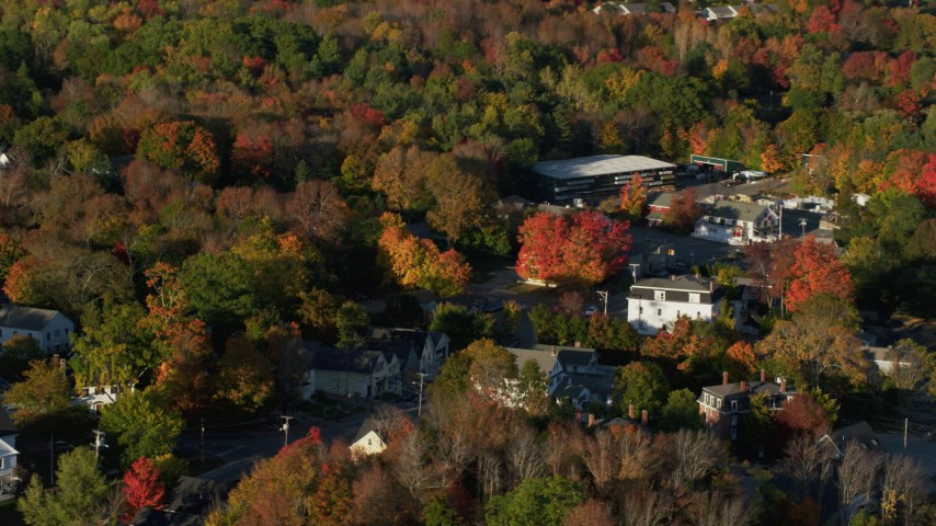 6K aerial video passing houses in a small town, fall foliage, Blue Hill, Maine Aerial Stock Footage | AX149_030
