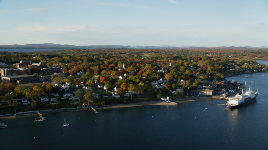 6K aerial video orbiting a coastal town, State of Maine training ship, among fall foliage, autumn, Castine, Maine Aerial Stock Footage | AX149_071