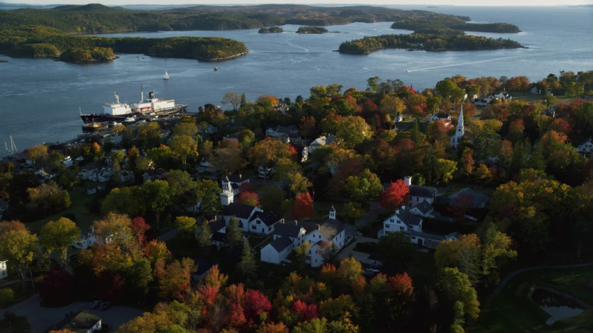 6K aerial video orbiting away from a small coastal town with fall foliage, autumn, Castine, Maine Aerial Stock Footage | AX149_077
