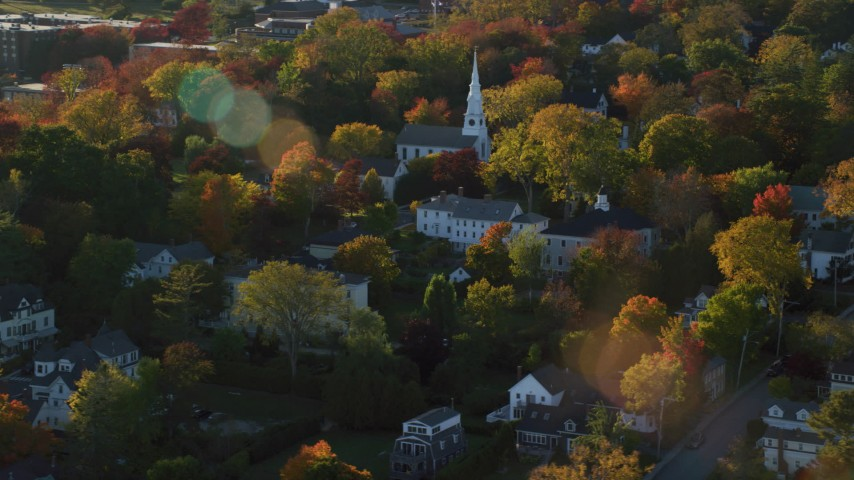 6K aerial video orbiting homes and a white church among fall foliage, autumn, Castine, Maine Aerial Stock Footage | AX149_078