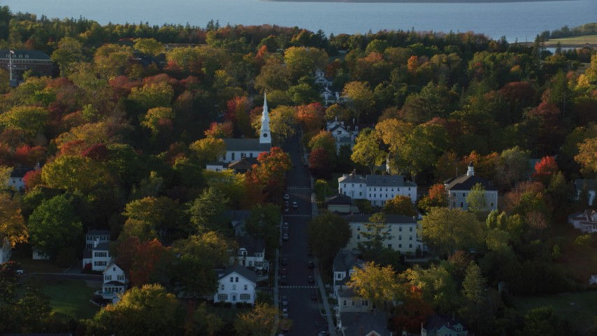 6K aerial video orbiting small town homes and white church in autumn, Castine, Maine Aerial Stock Footage | AX149_079