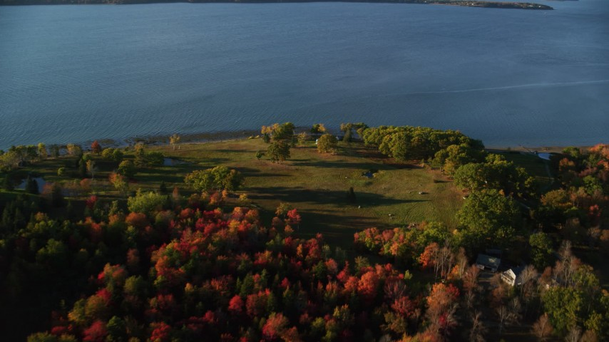 6K aerial video flying over colorful forest, approach rural waterfront homes, autumn, Castine, Maine Aerial Stock Footage | AX149_085