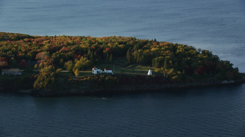 6K stock footage aerial video flying by Fort Point Light, among fall foliage, autumn, Stockton Springs, Maine Aerial Stock Footage | AX149_088