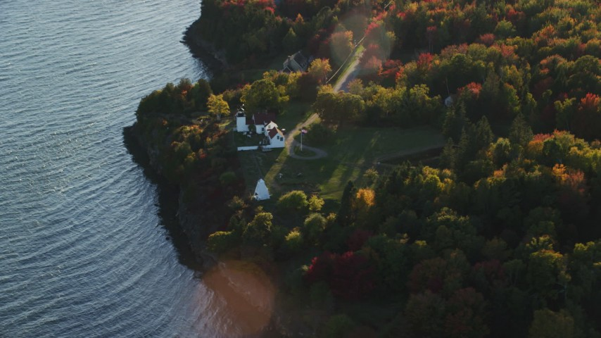 6K stock footage aerial video flying by Fort Point Light, colorful trees in autumn, Stockton Springs, Maine Aerial Stock Footage | AX149_089