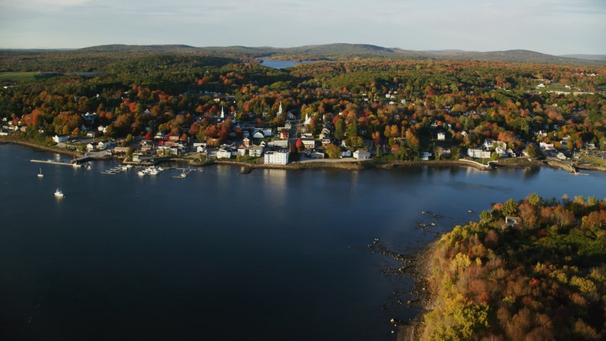 6K aerial video flying by small coastal town, colorful trees in autumn, Bucksport, Maine Aerial Stock Footage | AX149_103