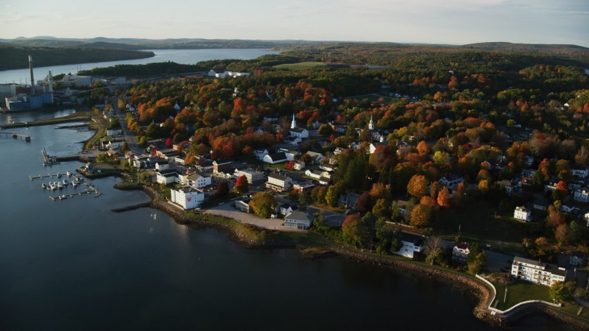 6K aerial video orbiting small coastal town, colorful trees, autumn, Bucksport, Maine Aerial Stock Footage AX149_104