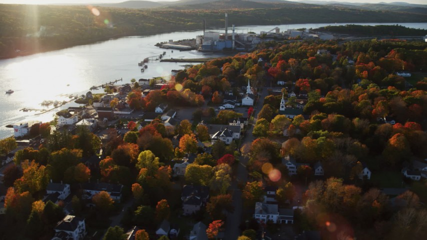 6K aerial video orbiting a small coastal town nestled among fall foliage, autumn, Bucksport, Maine Aerial Stock Footage | AX149_105