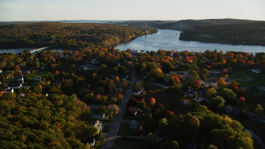 6K aerial video approaching Penobscot Narrows Bridge from over small town, autumn, Bucksport, Maine Aerial Stock Footage | AX149_111