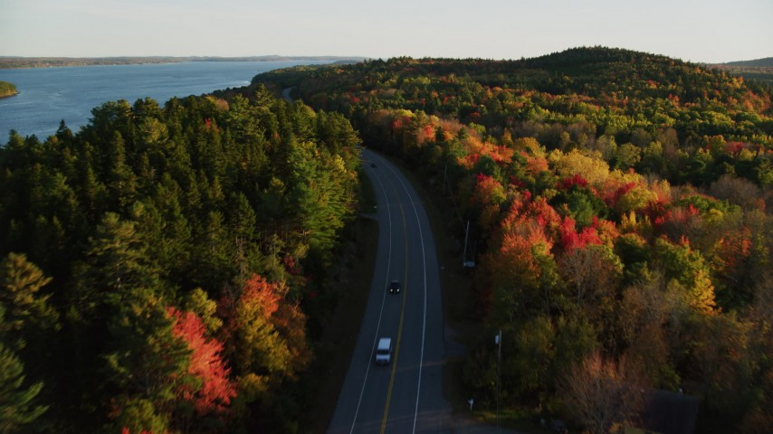 6K aerial video flying over road among forest of fall foliage, autumn, Stockton Springs, Maine, sunset Aerial Stock Footage | AX149_119
